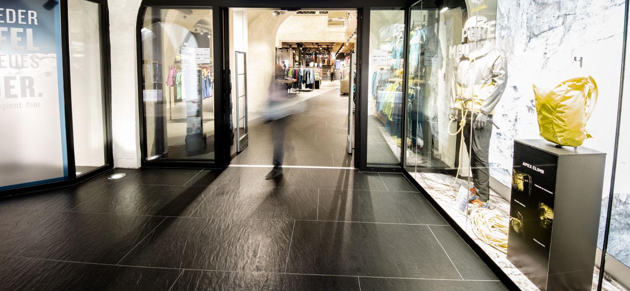 Verlegung von eleganten schwarzen Fliesen im Kontrast am Eingang von Sportler Alpin unter den Lauben in Bozen vom Renovierungs-Experten Baustudio in Südtirol.